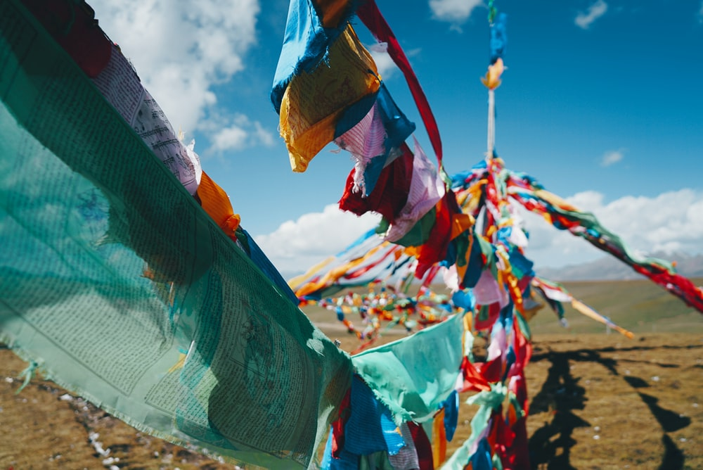 assorted-color textile hangs under clear blue sky during daytime