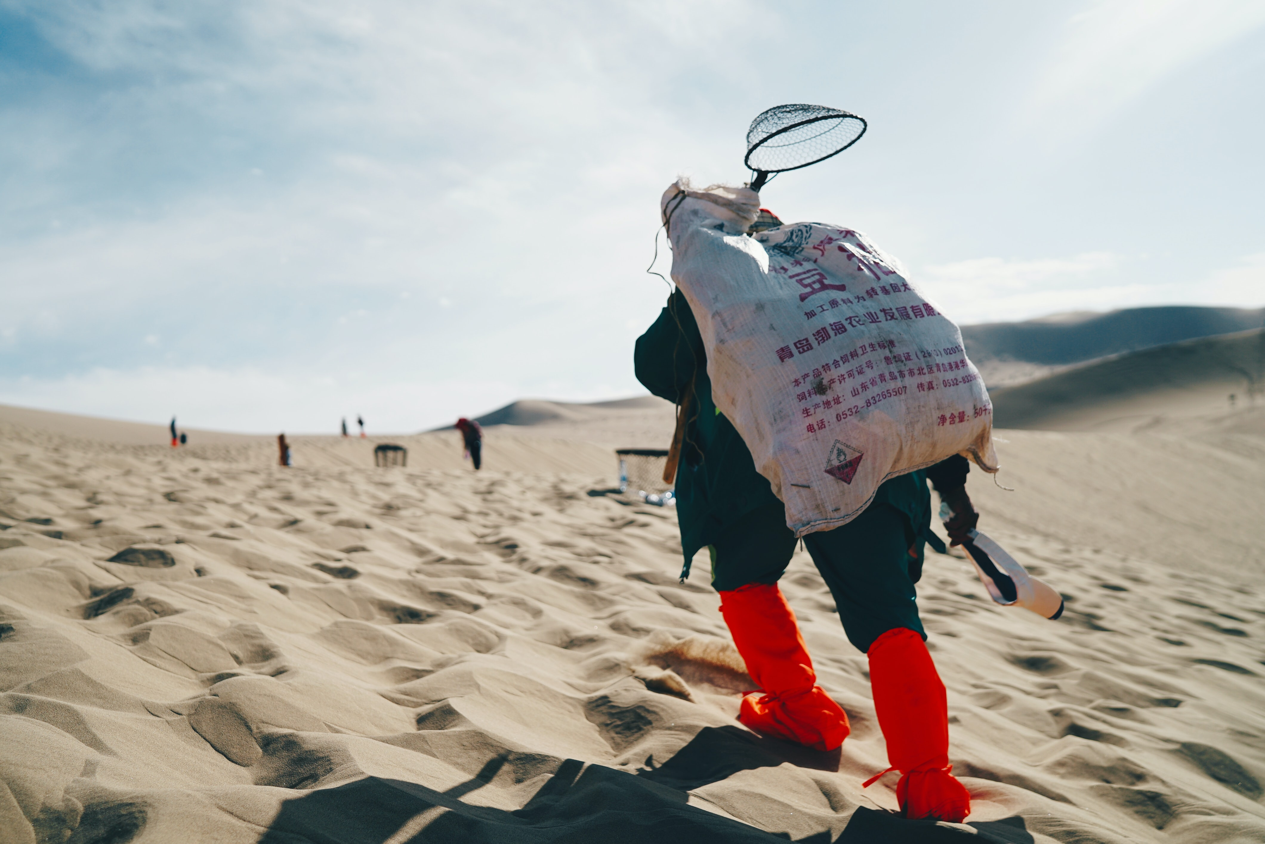 person carrying sack in the desert
