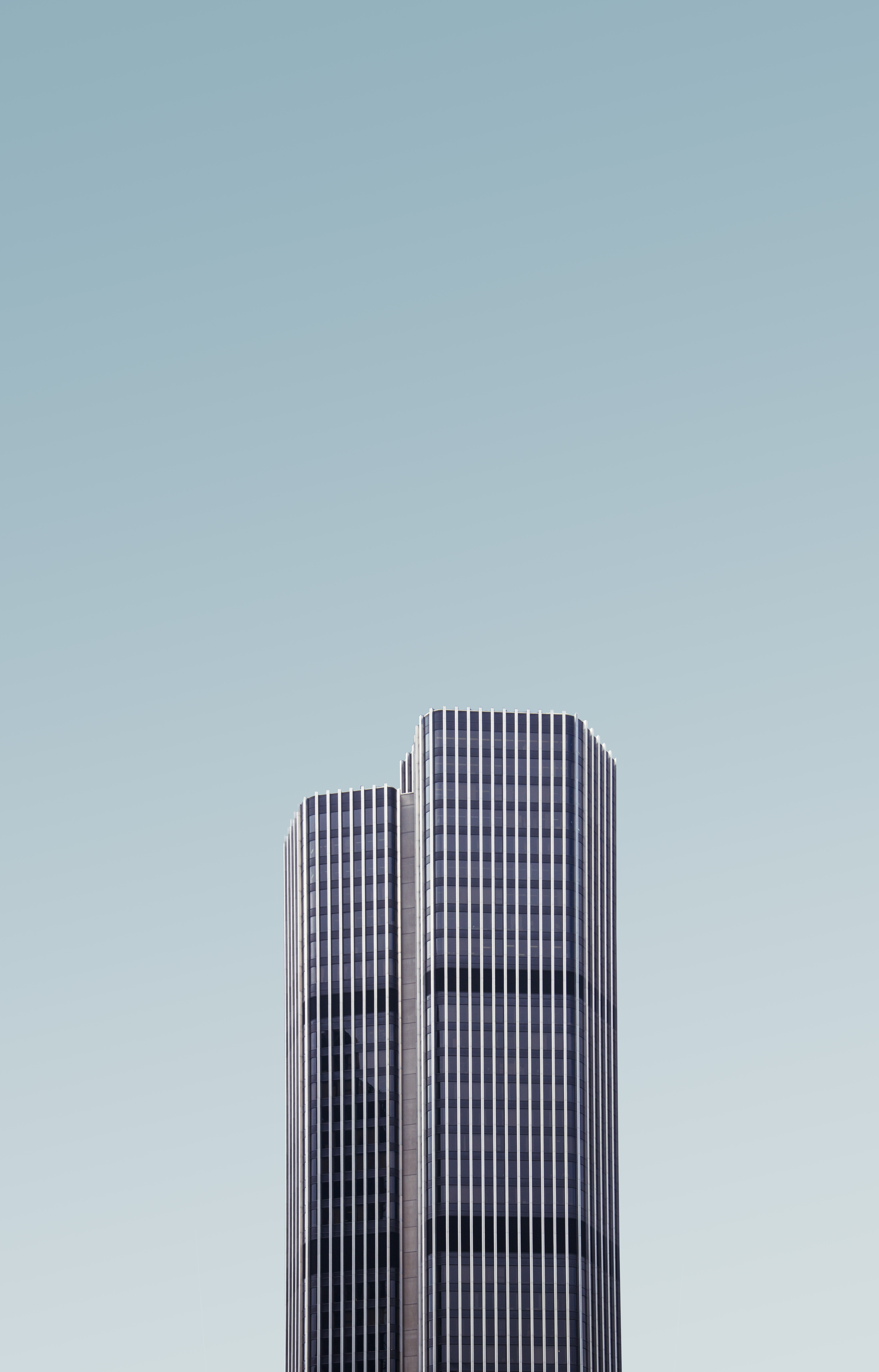 grey and white high-rise building under white cloudy sky