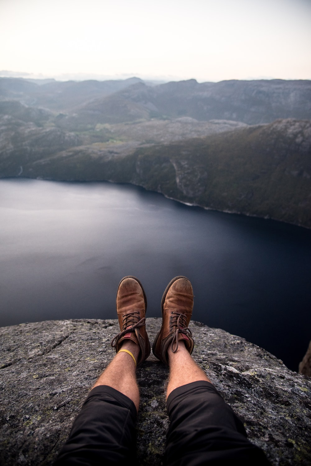 person wearing brown boots sitting on cliff in front of grey calm body of water and rock formations during daytime