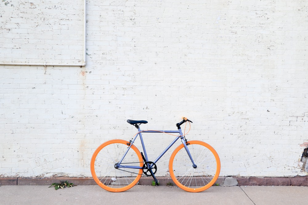 yellow and purple bicycle near white wall at daytime