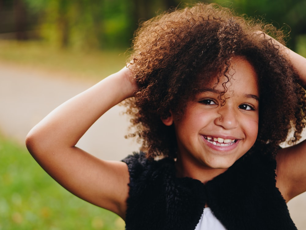 hair porosity: young girl touching natural hair