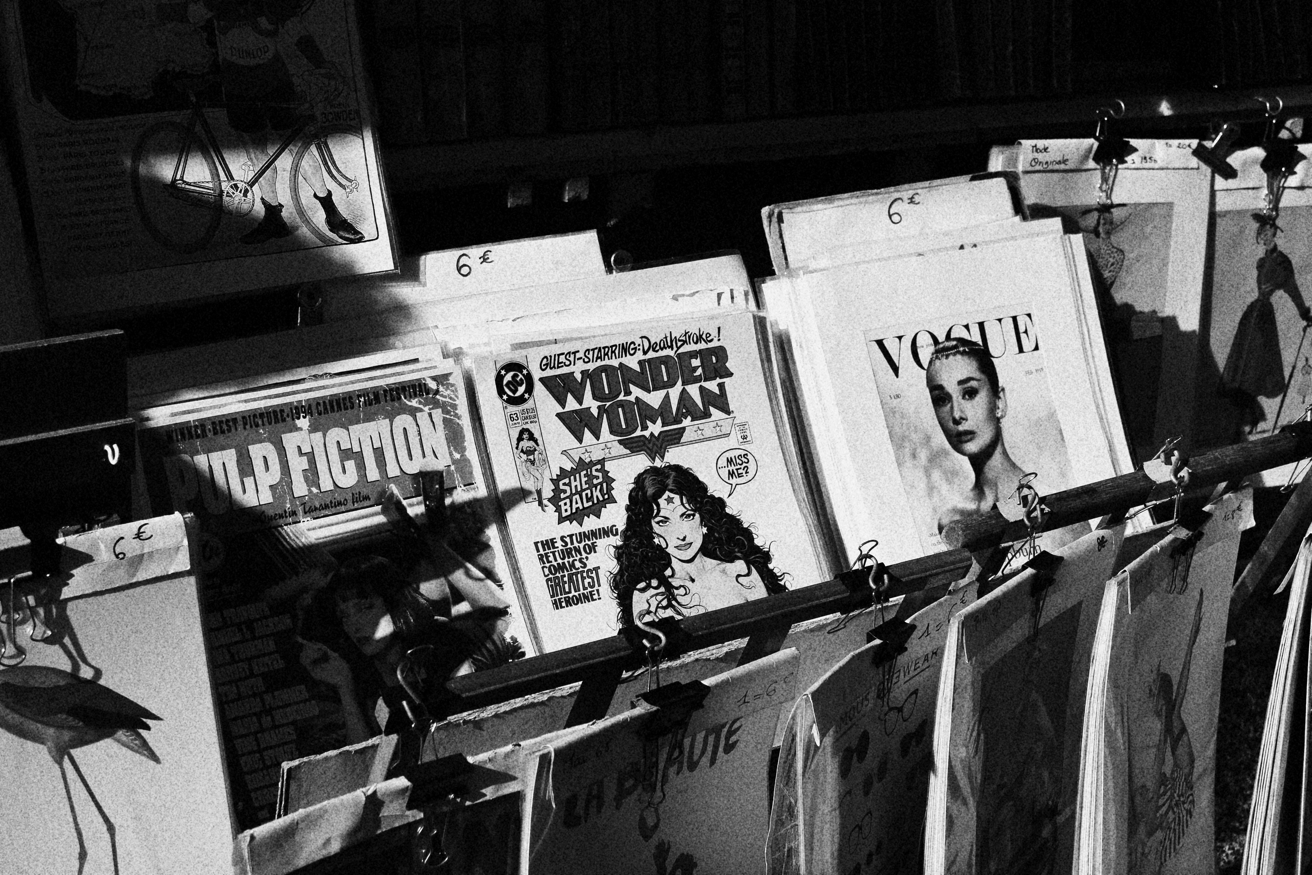 grayscale photo of magazines on rack