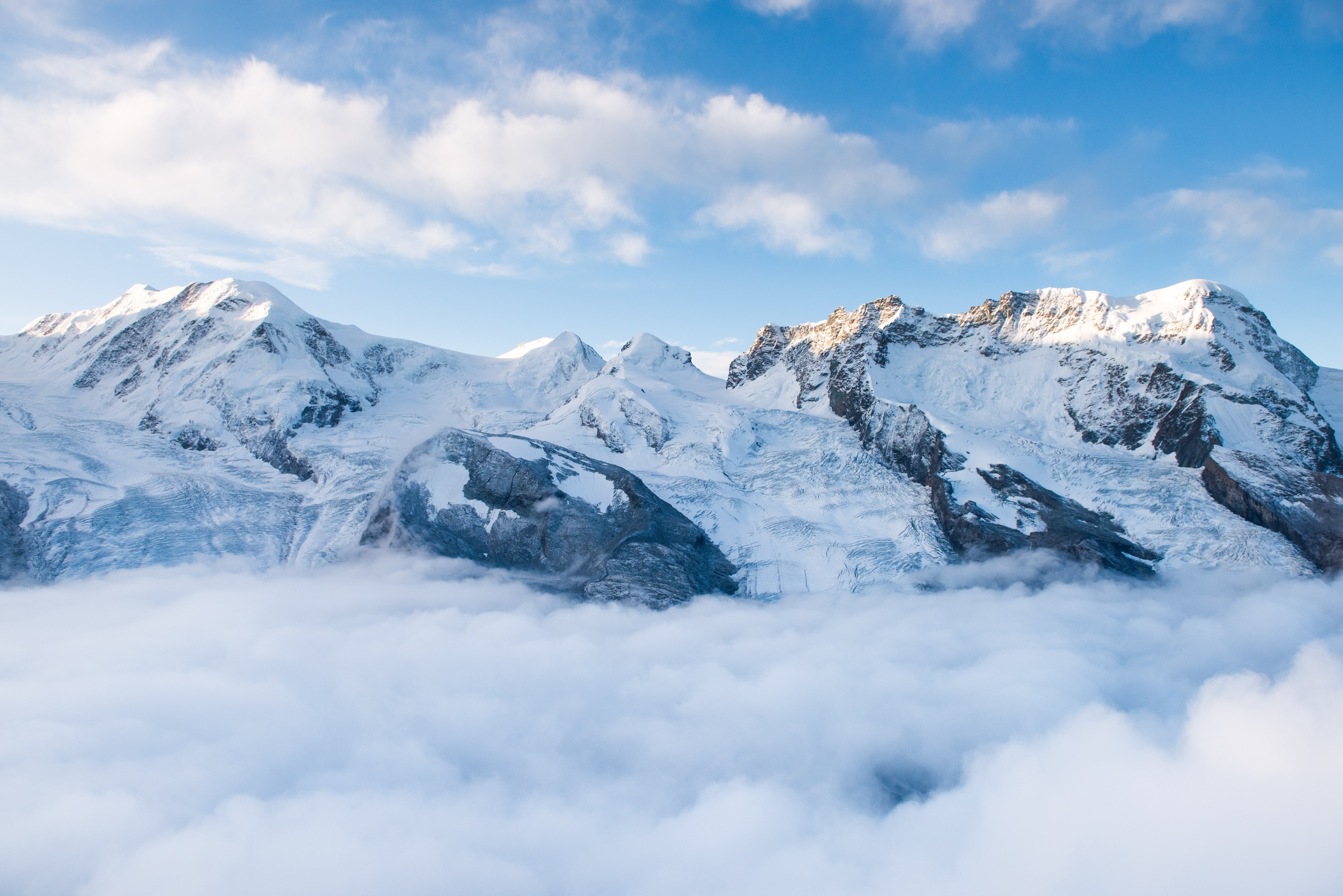 snow-capped mountain with sea of clouds