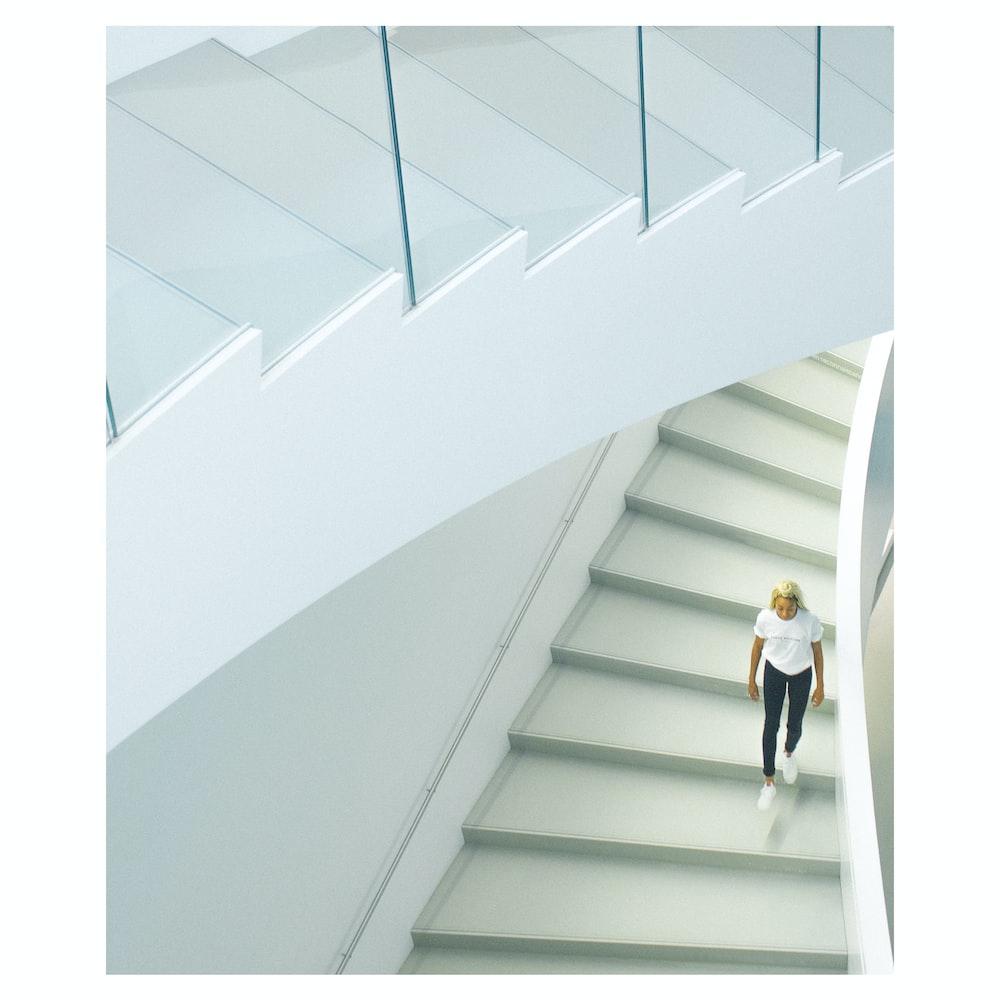 woman wearing white crew-neck t-shirt walking on stairs