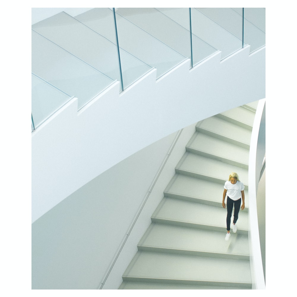 woman wearing white crew-neck t-shirt walking on stairs