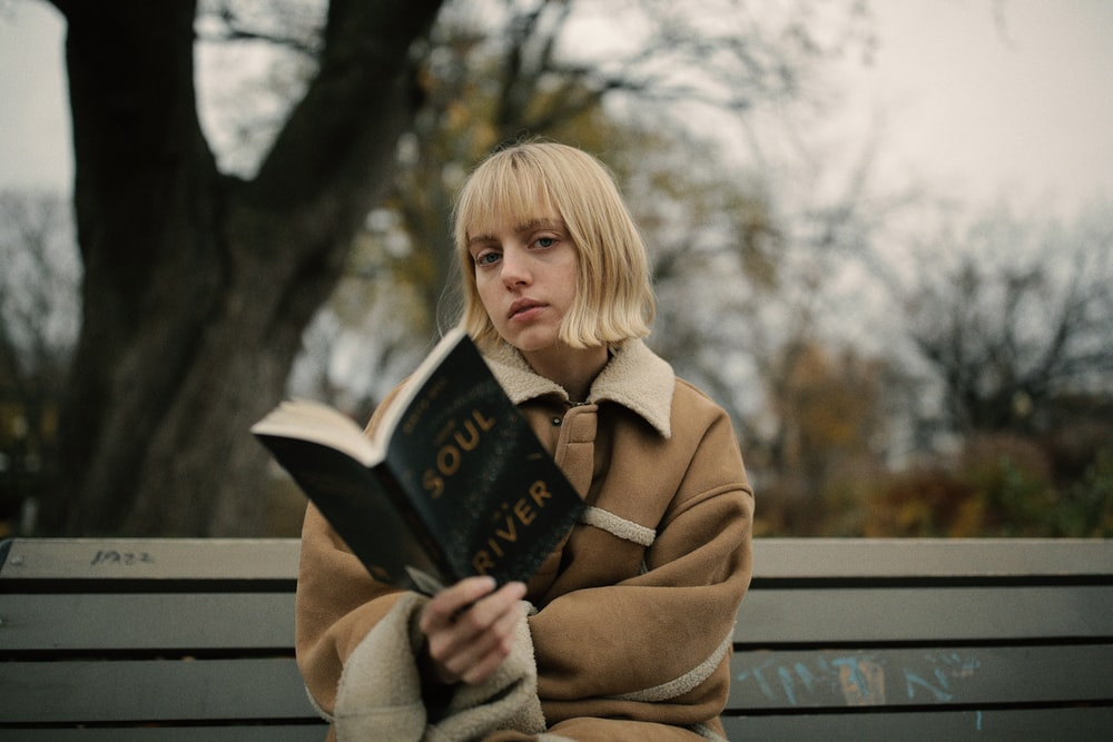 woman holding book while sitting on gray bench