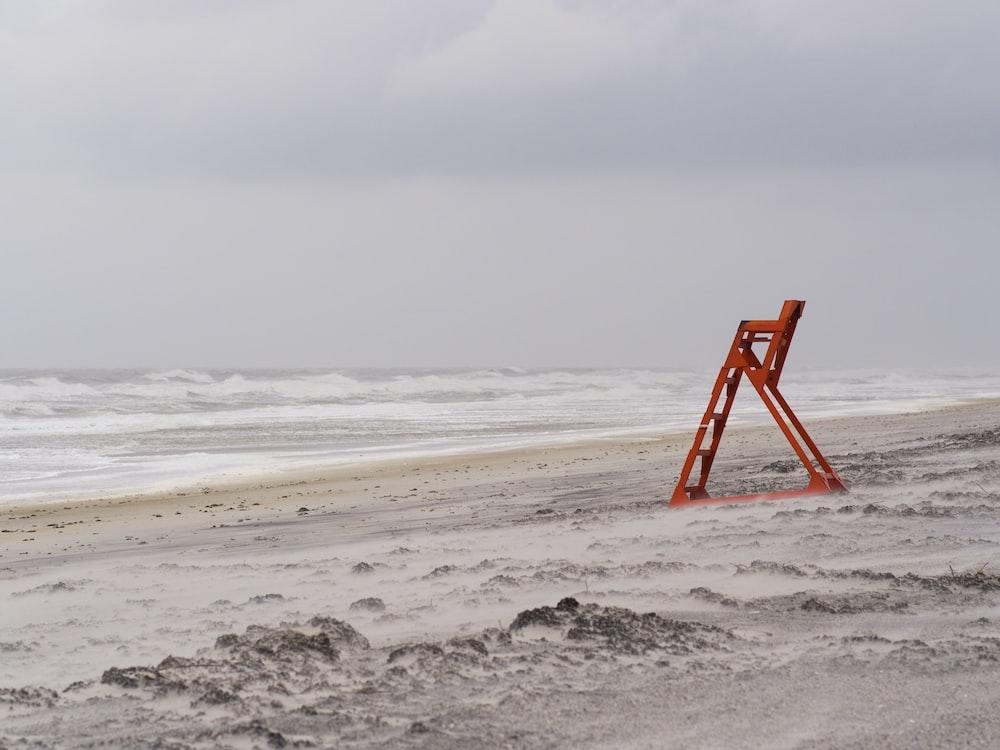 red metal ladder stand near seashore during daytime
