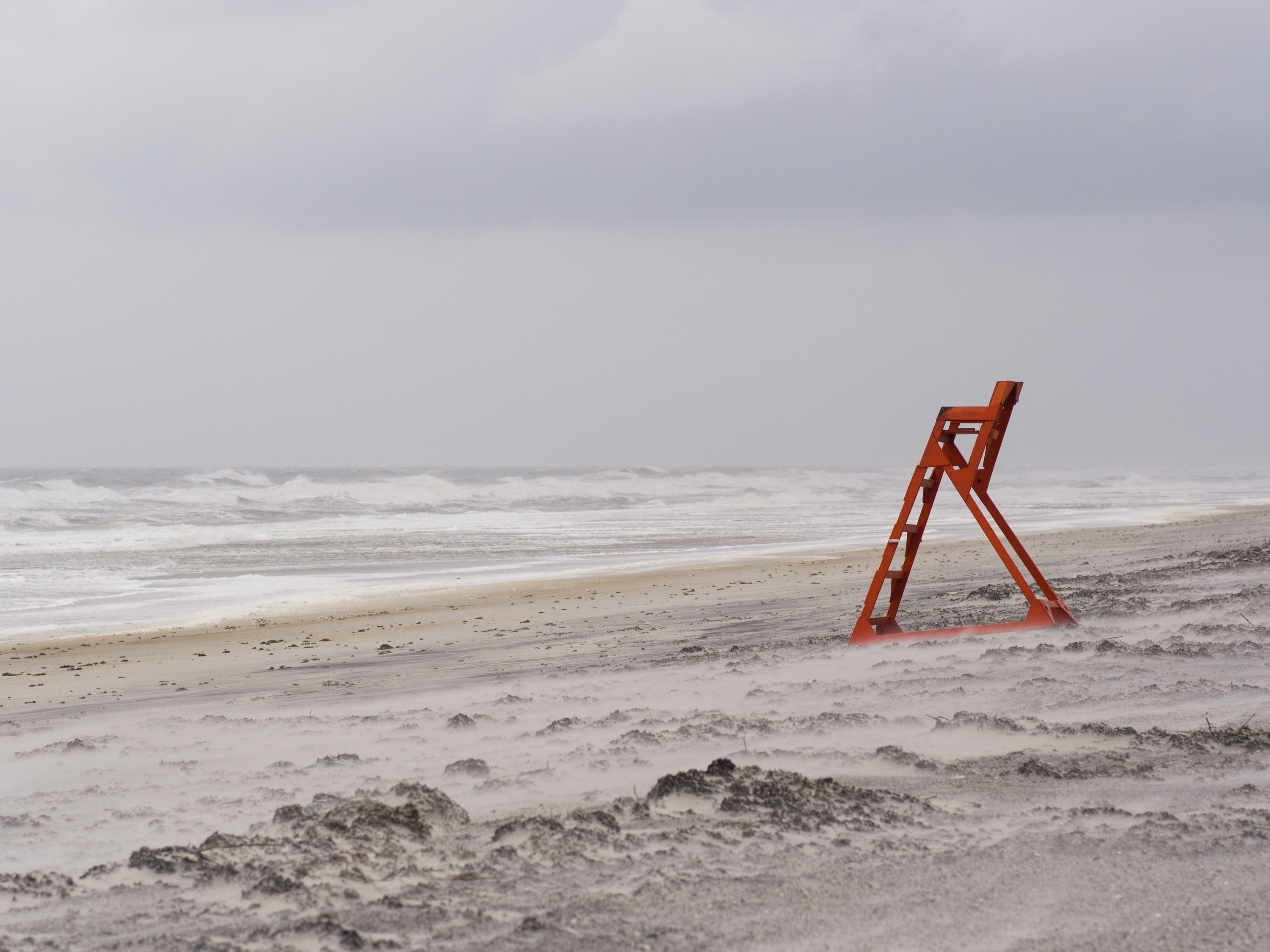 red metal ladder stand near seashore during daytime
