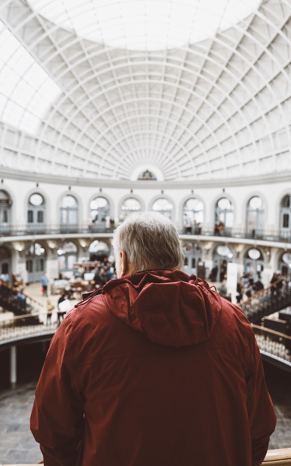 man wearing red hoodie inside dome building in front of people