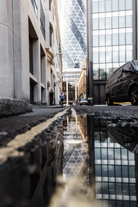 puddle on roadside showing reflection of black vehicle beside highrise buildings