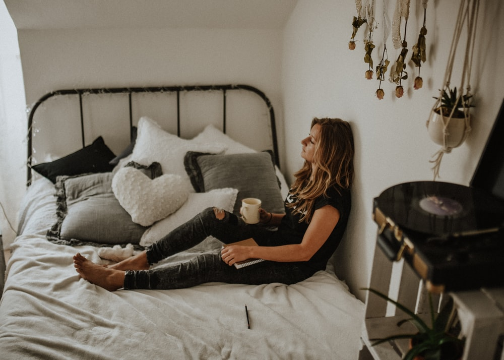 woman leaning on wall while sitting on bed