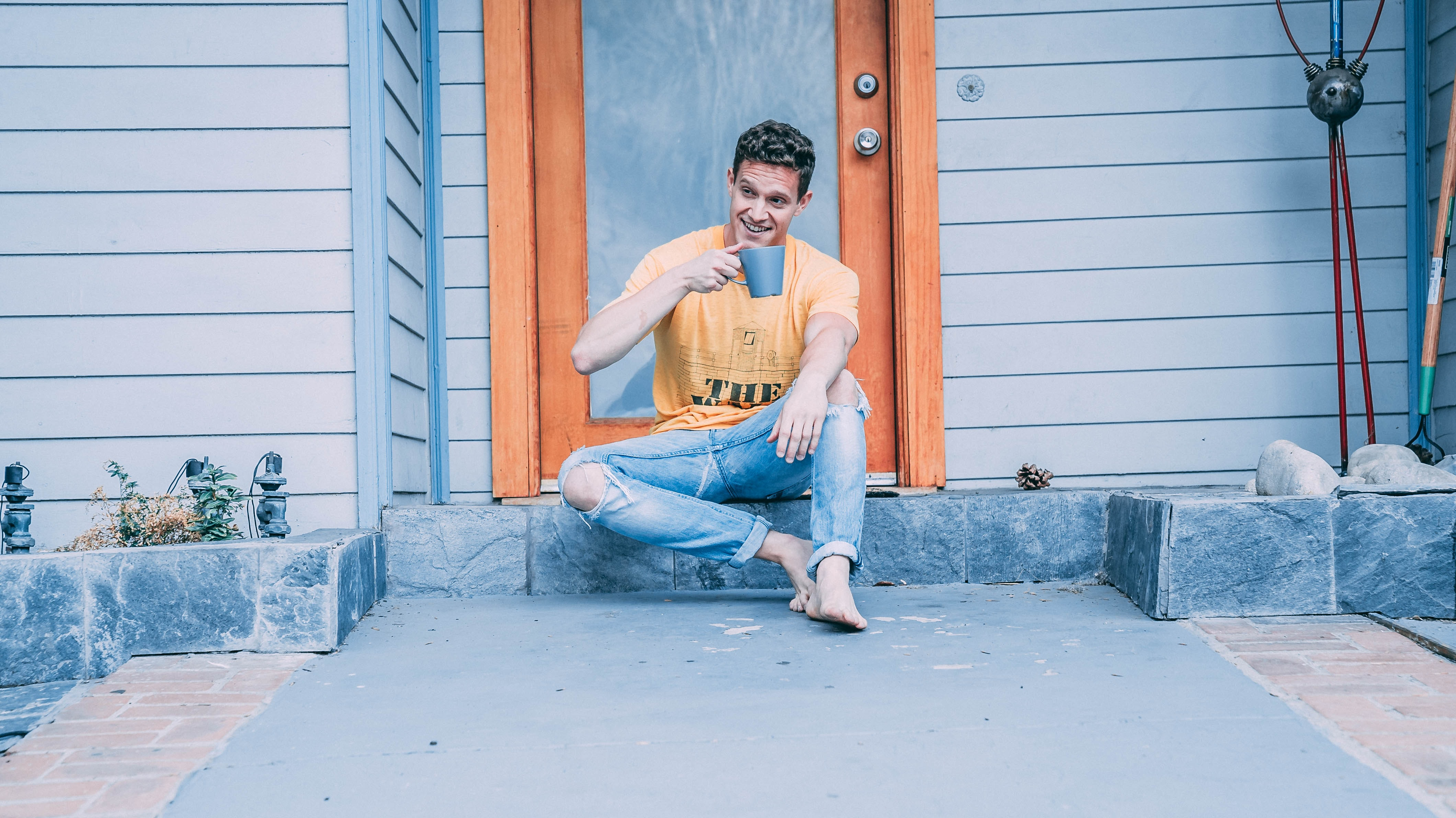 man sitting while holding cup during daytime