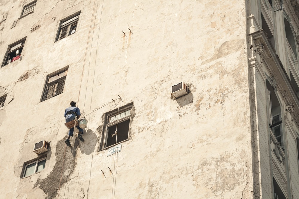 man painting white concrete building during daytime while hanging