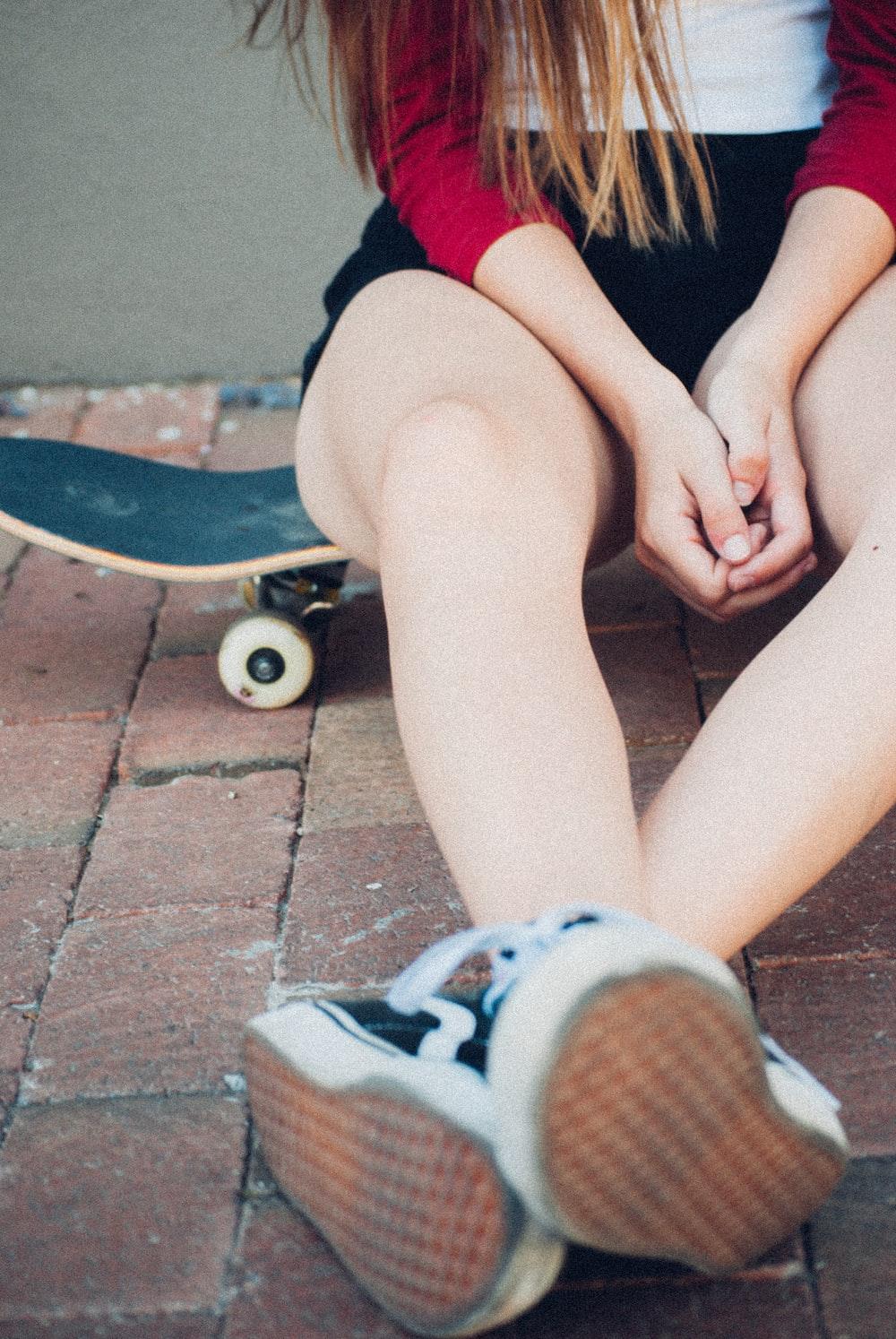 woman sitting on black skateboard during daytime