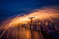 steel wool photography of person standing on sea dock