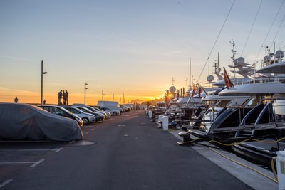 cars in front of yacht during sunset