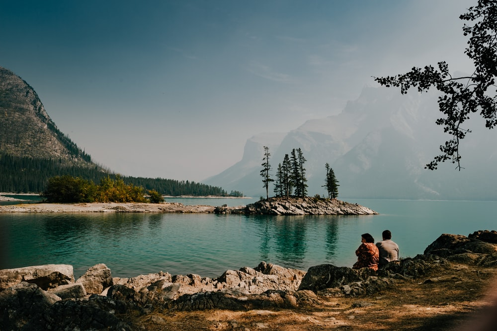 two person sitting down on rock near body of water during daytime