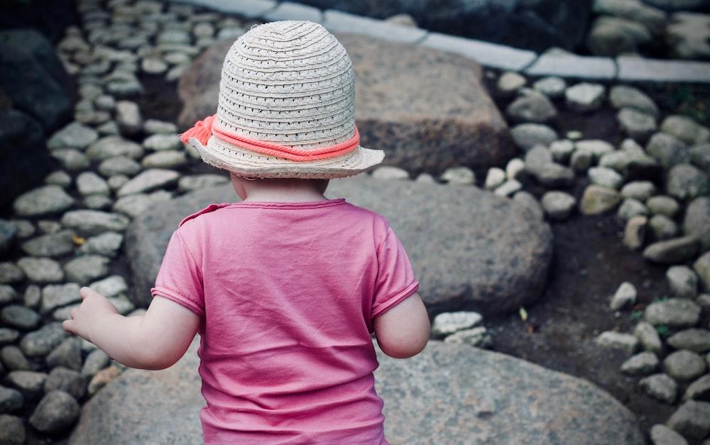 child walking on gray rock during daytime