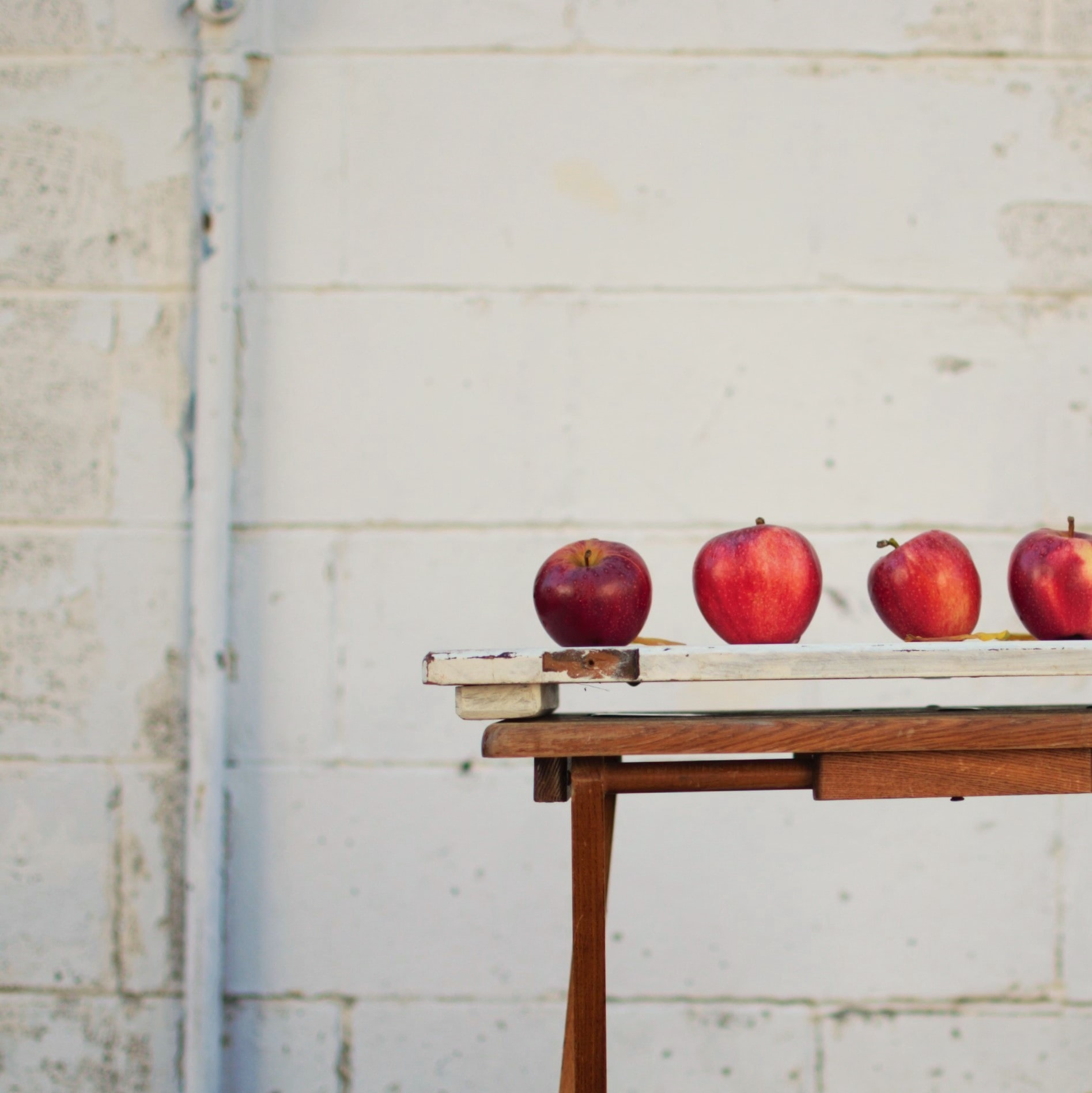 red apples on white wooden board
