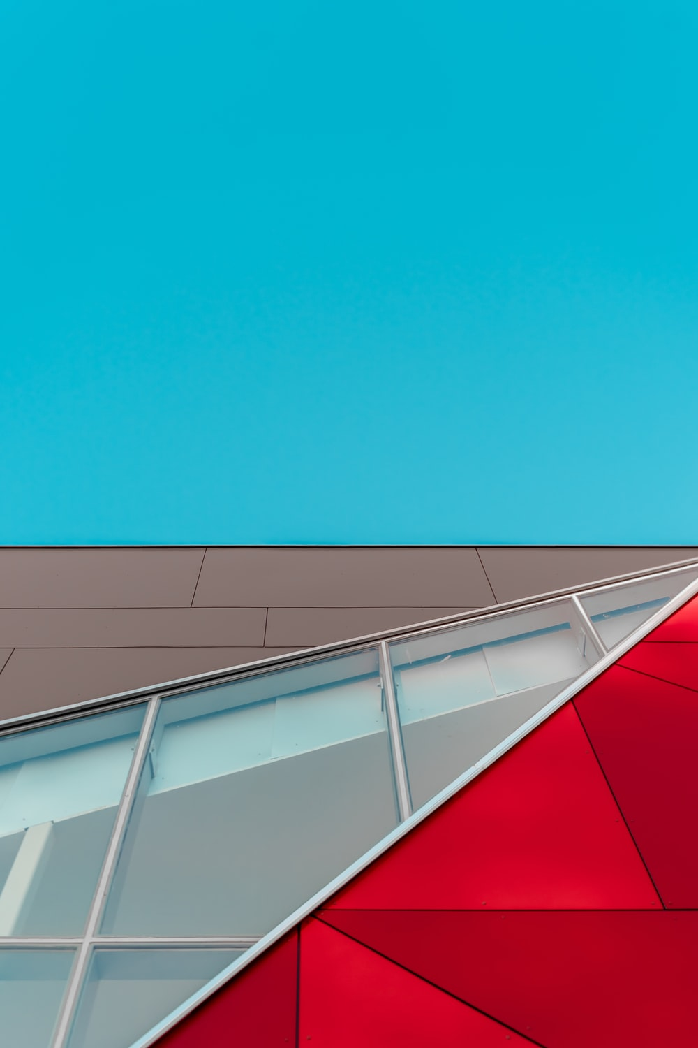 shallow focus photography of red, brown, and white glass panel wall building under blue sky