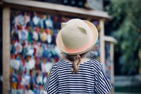 person standing near stall wearing straw hat