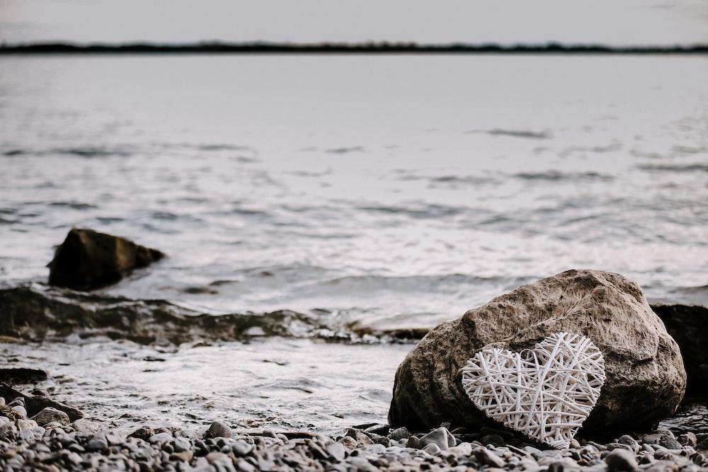 heart-shaped string artwork leaning on brown rock near shoreline at daytime