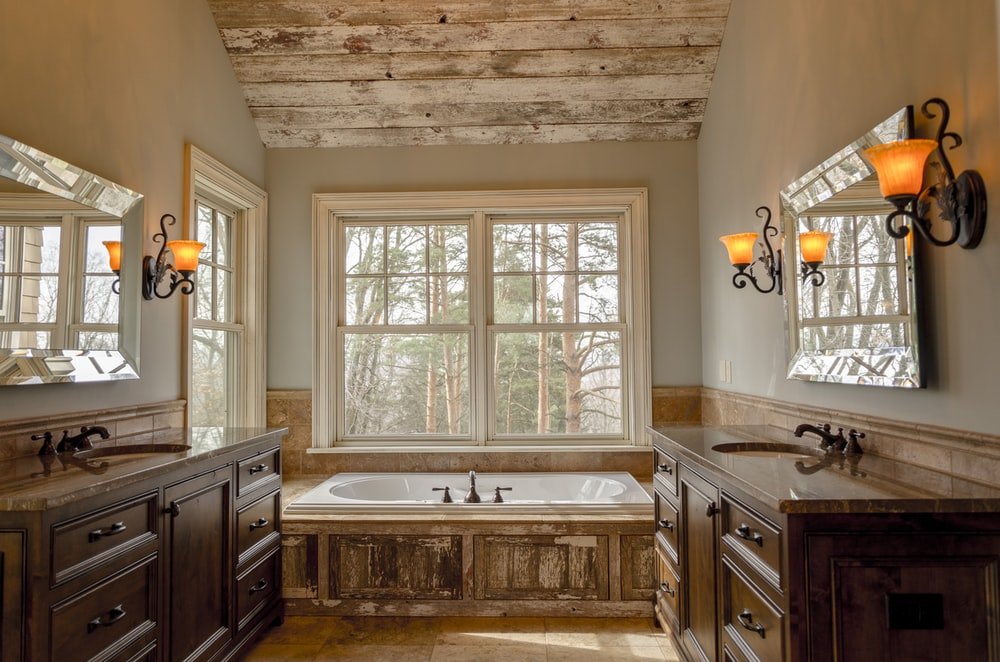 comfort room with white bathtub and brown wooden cabinets