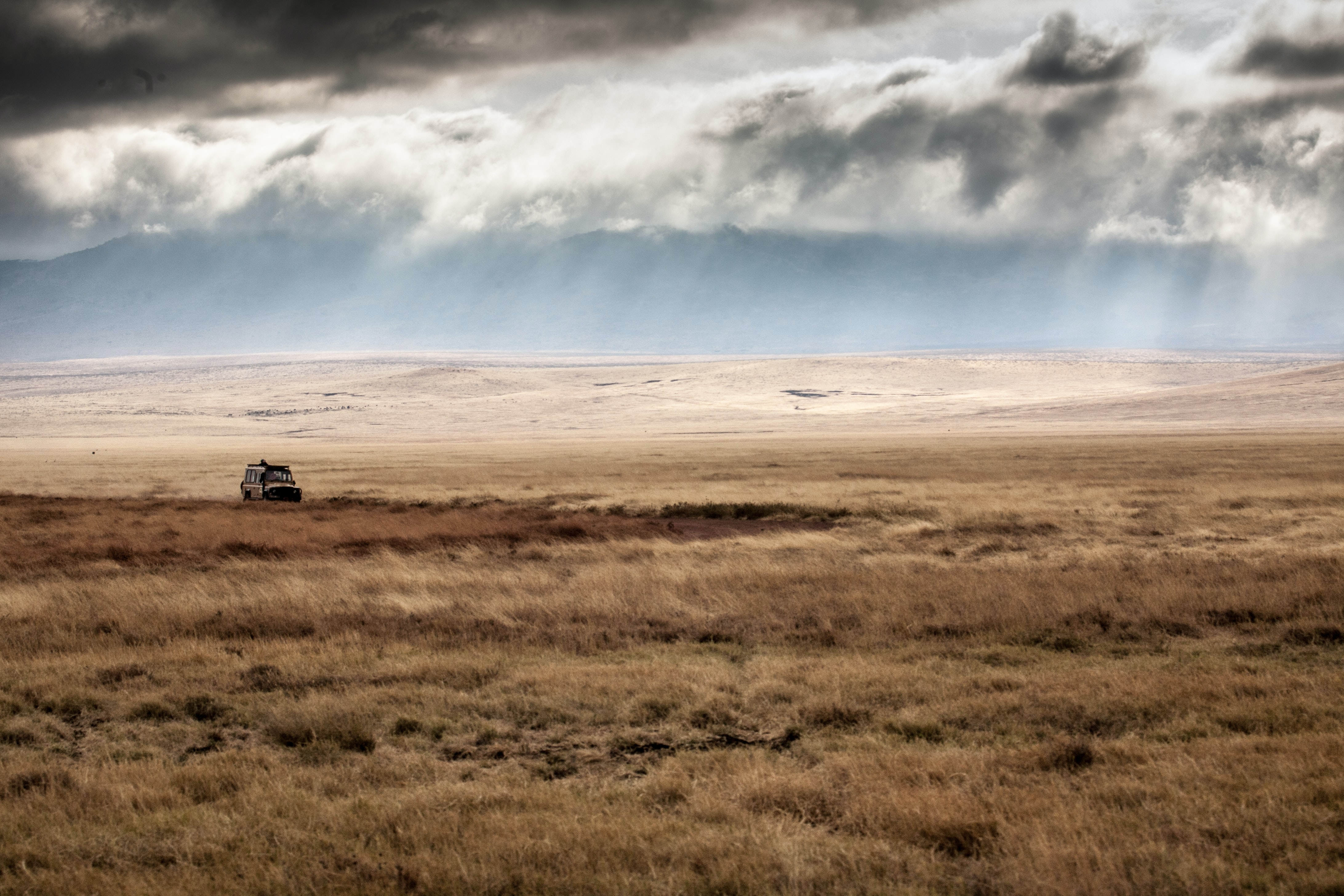 car on brown field under white clouds and blue sky