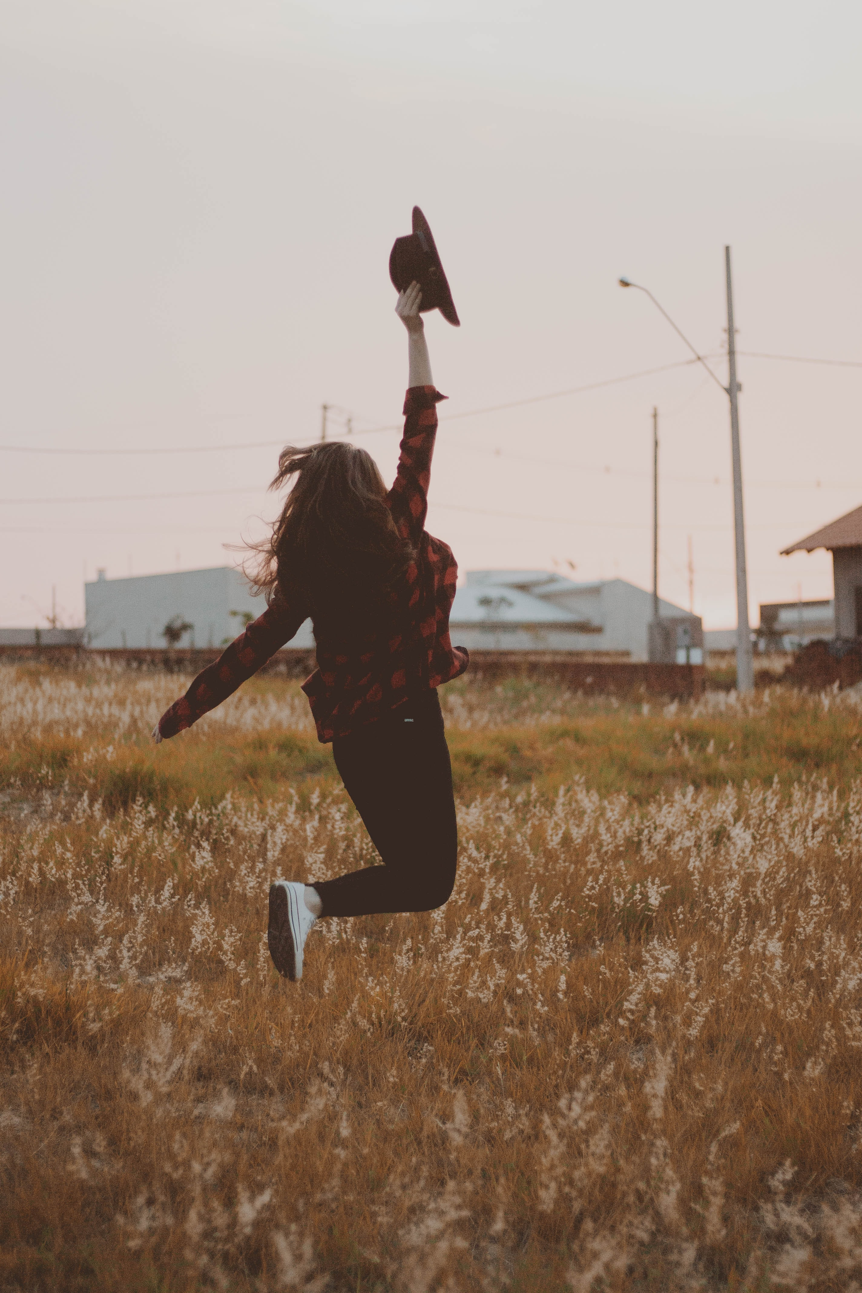 woman jumping while holding cap