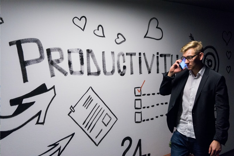Flexible Office Productivity man holding smartphone looking at productivity wall decor