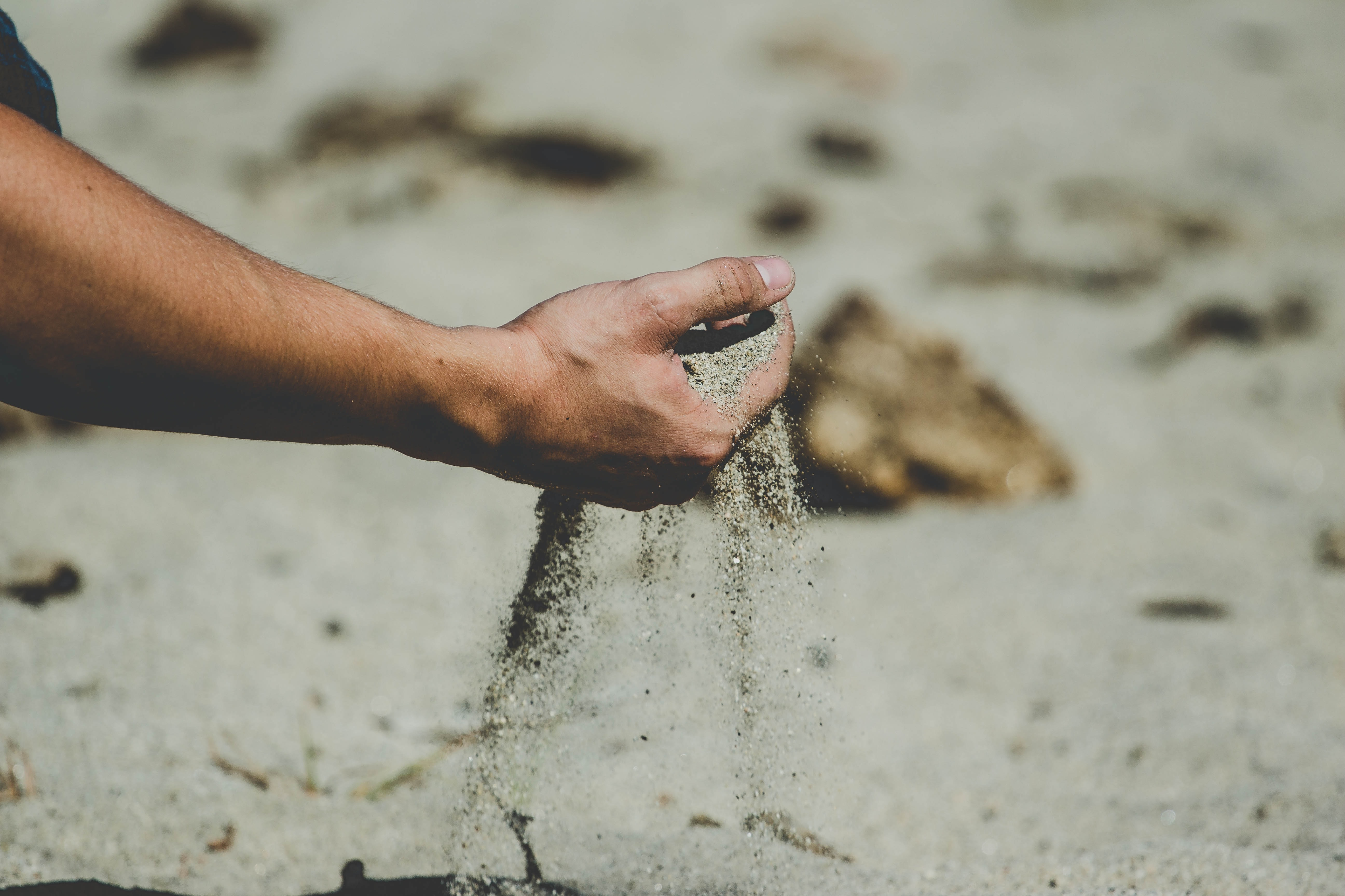 person holding brown sand