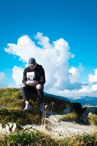 man sitting on rock on top of hill while holding quadcopter drone under cloudy sky during daytime