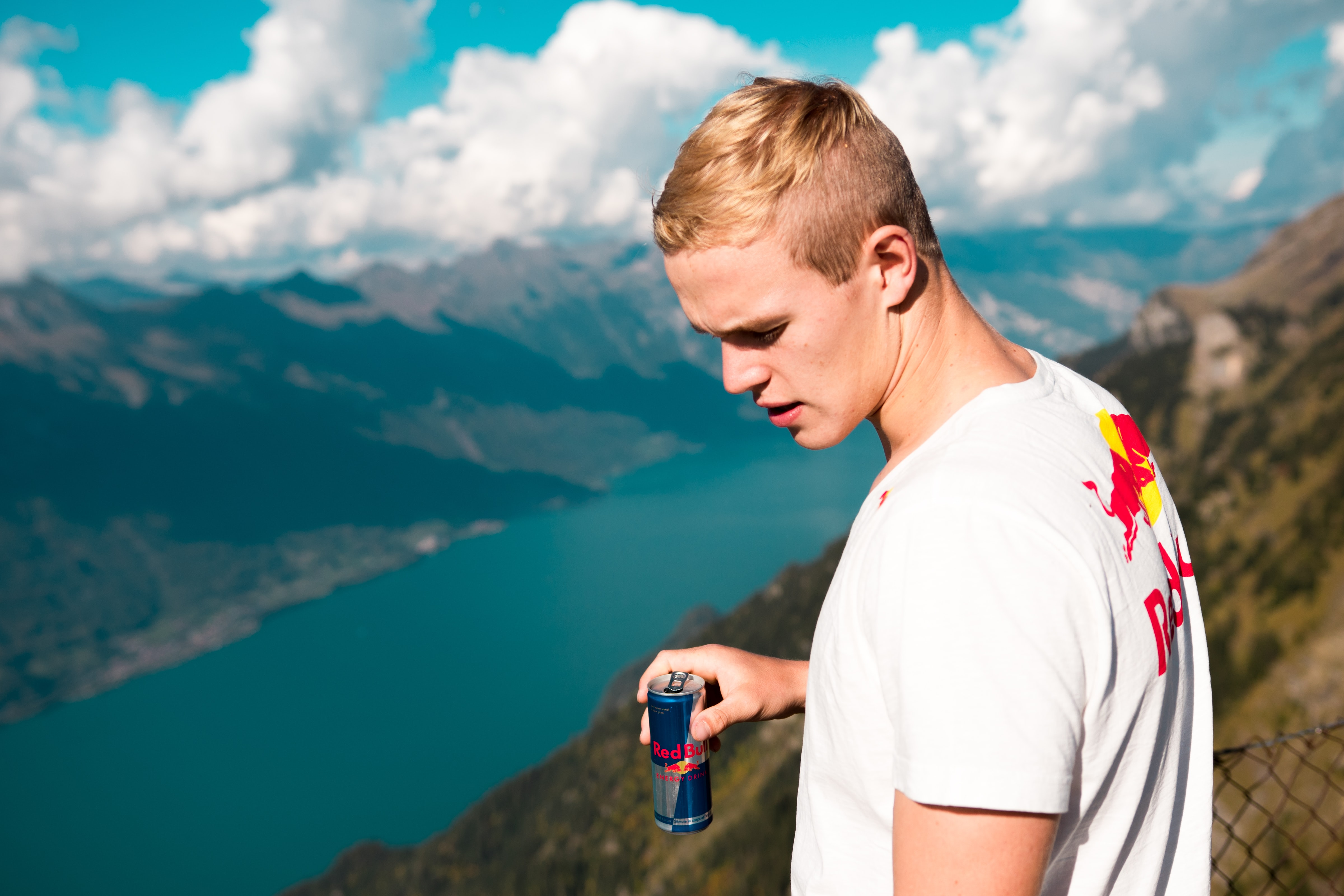 man wearing white and red crew-neck t-shirt holding Red Bull energy drink can standing on summit with chain link fence looking at body of water during daytime
