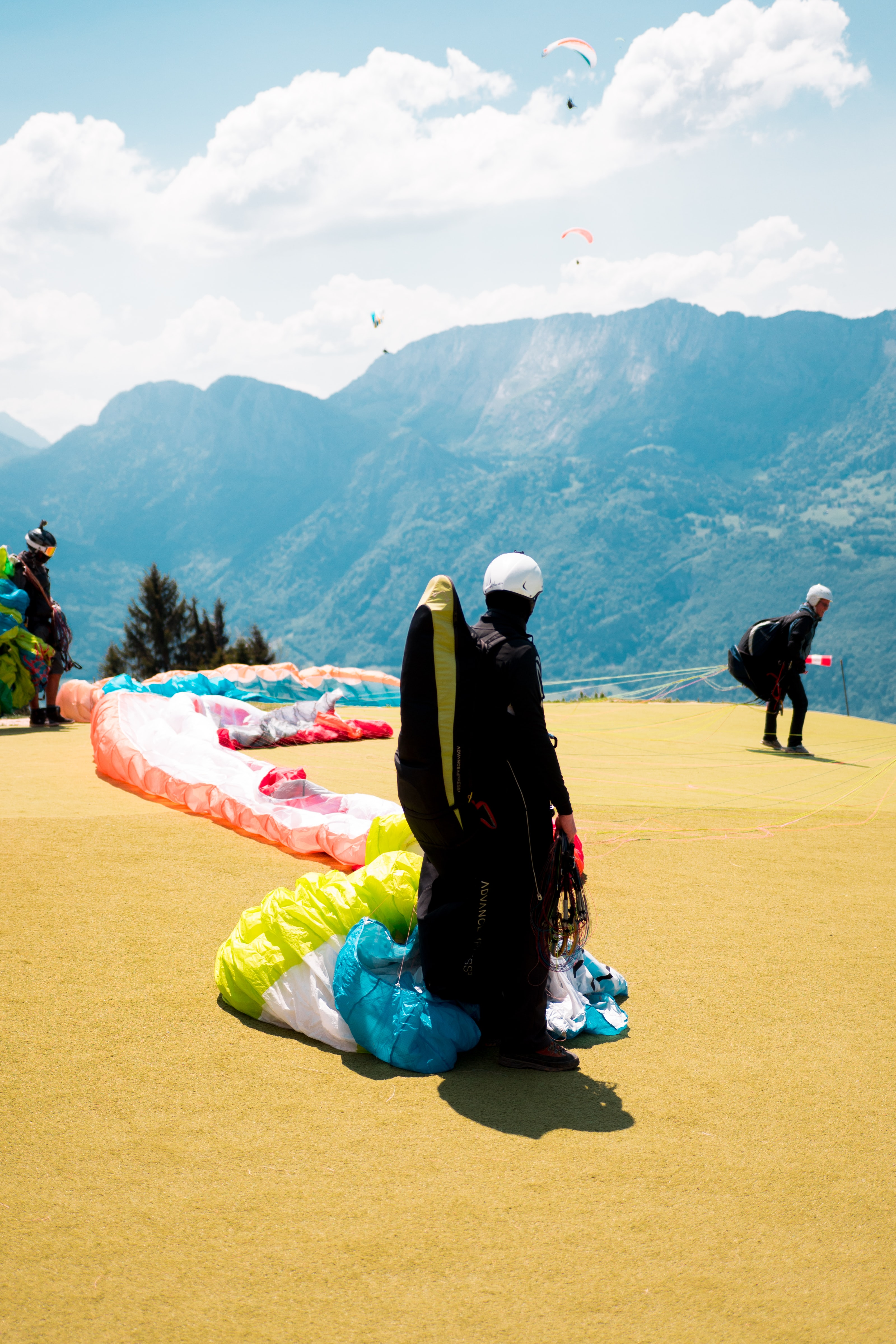 paraglider buckled in black, yellow, and blue parachute while standing on yellow hill near man preparing to jump overlooking mountain ridges under white cloudy skies at daytime