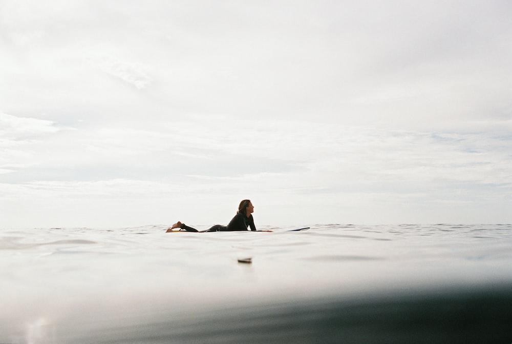 woman lying on surfboard on body of water