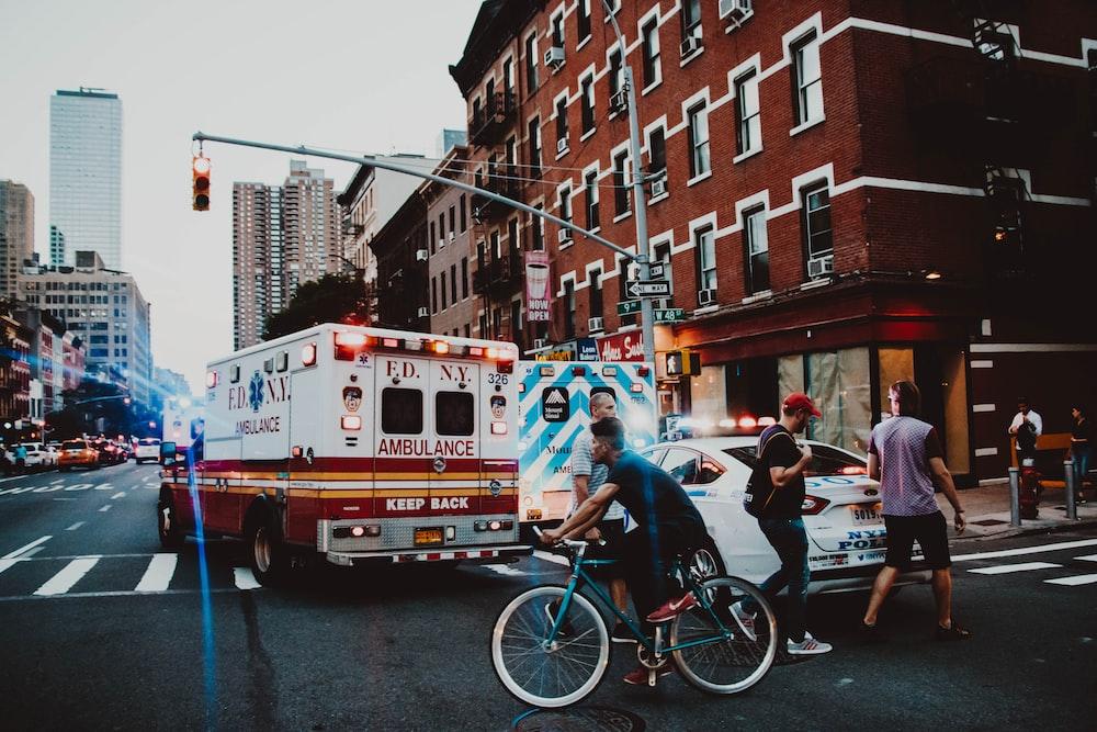 three people walking near man riding bicycle on street near ambulance