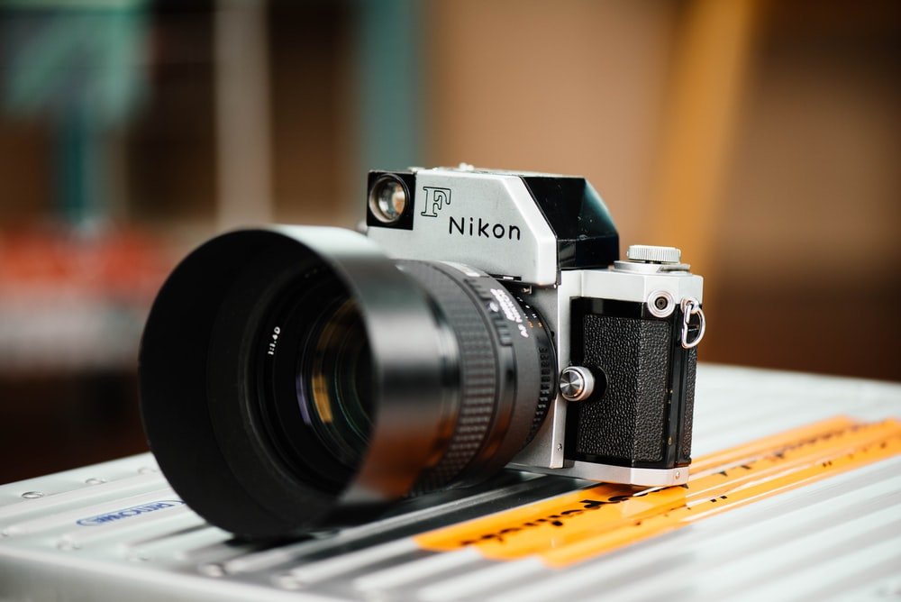 white and black Nikon DSLR camera on top of grey surface