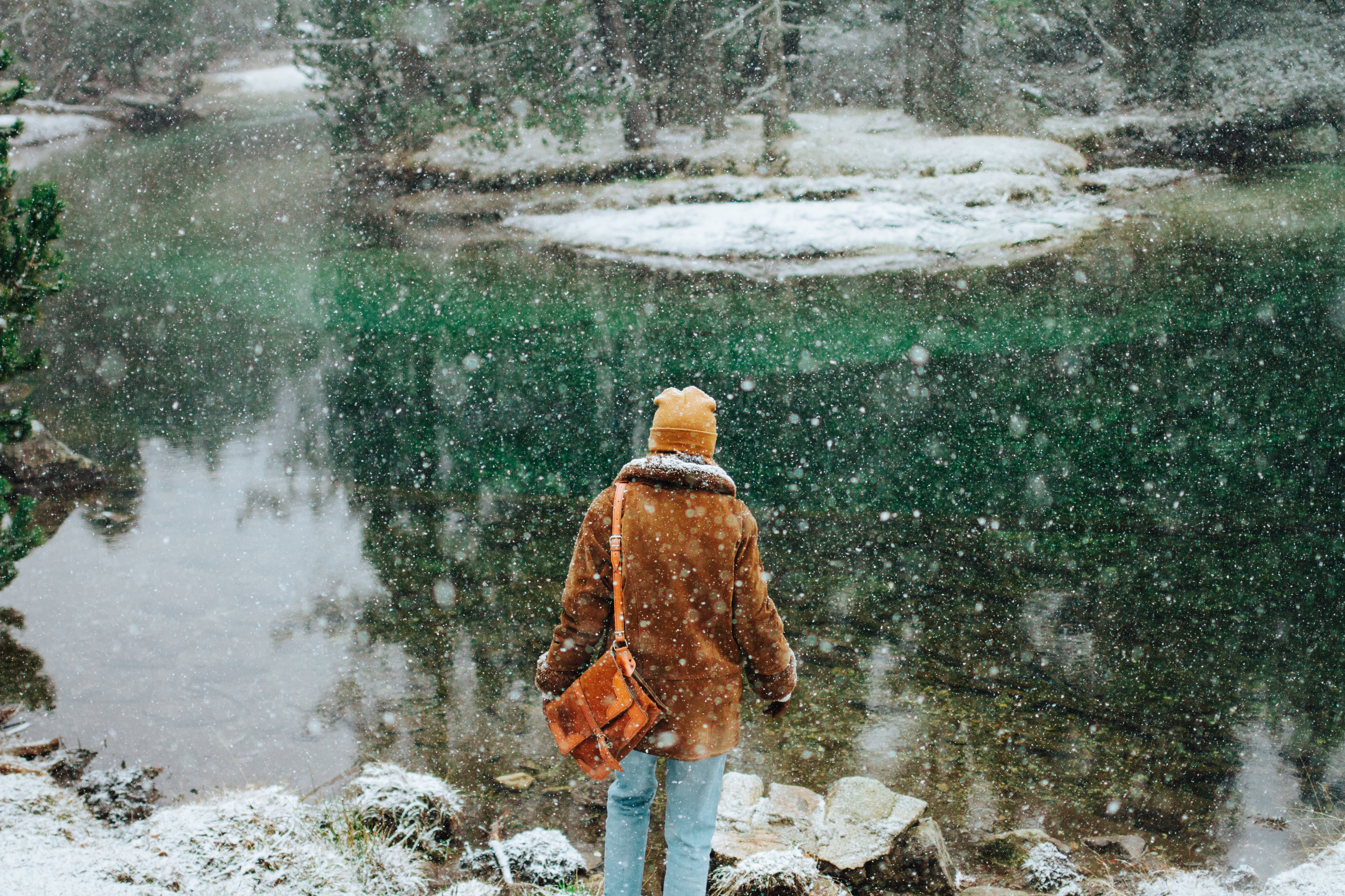 person wearing jacket standing near body of water