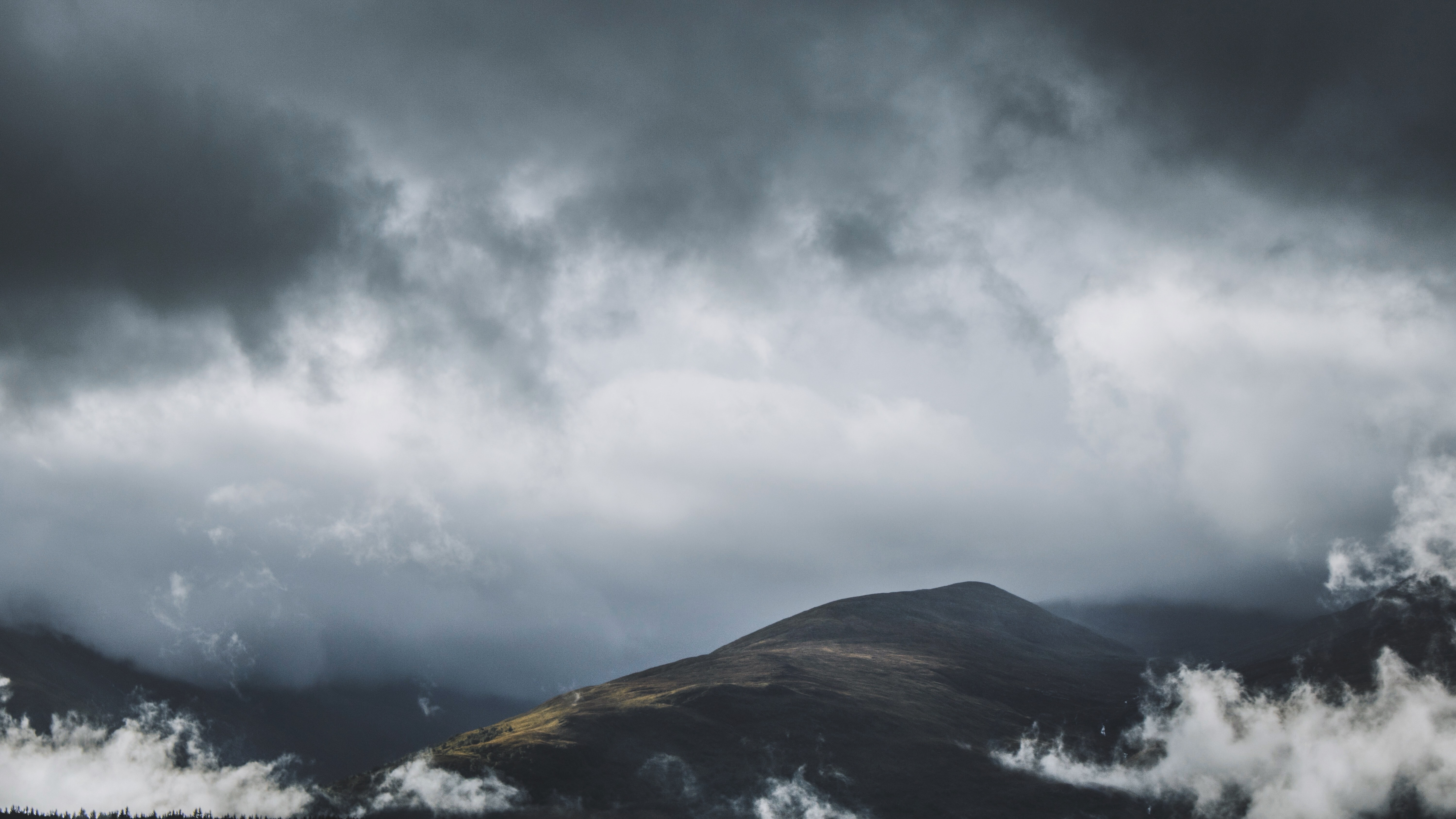 brown and black hill under cloudy sky during daytime