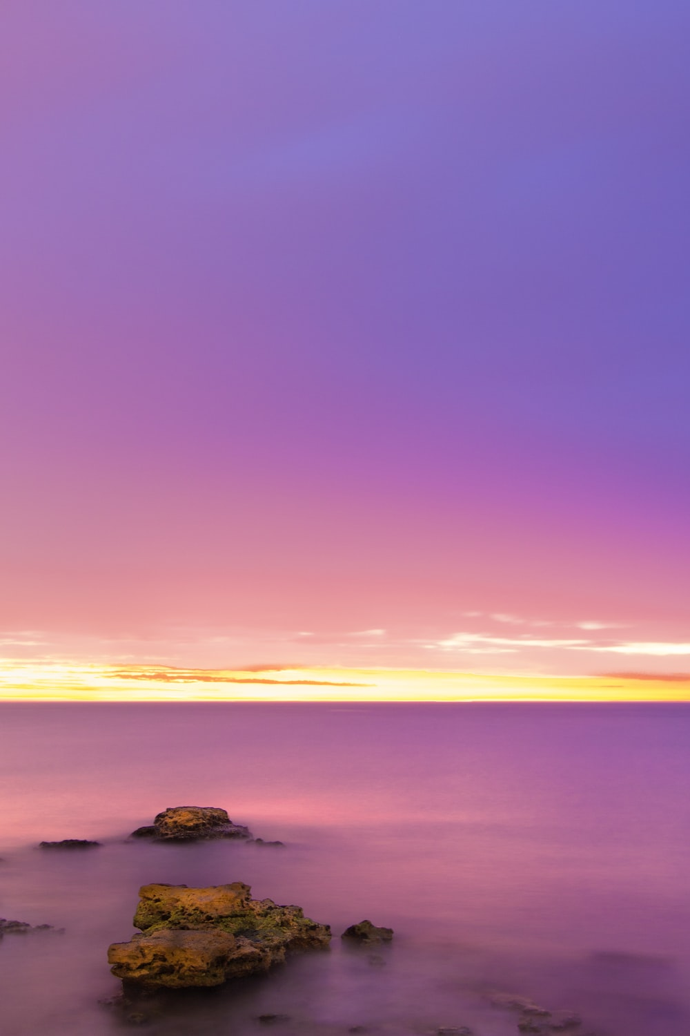 rock formation on body of water during sunrise
