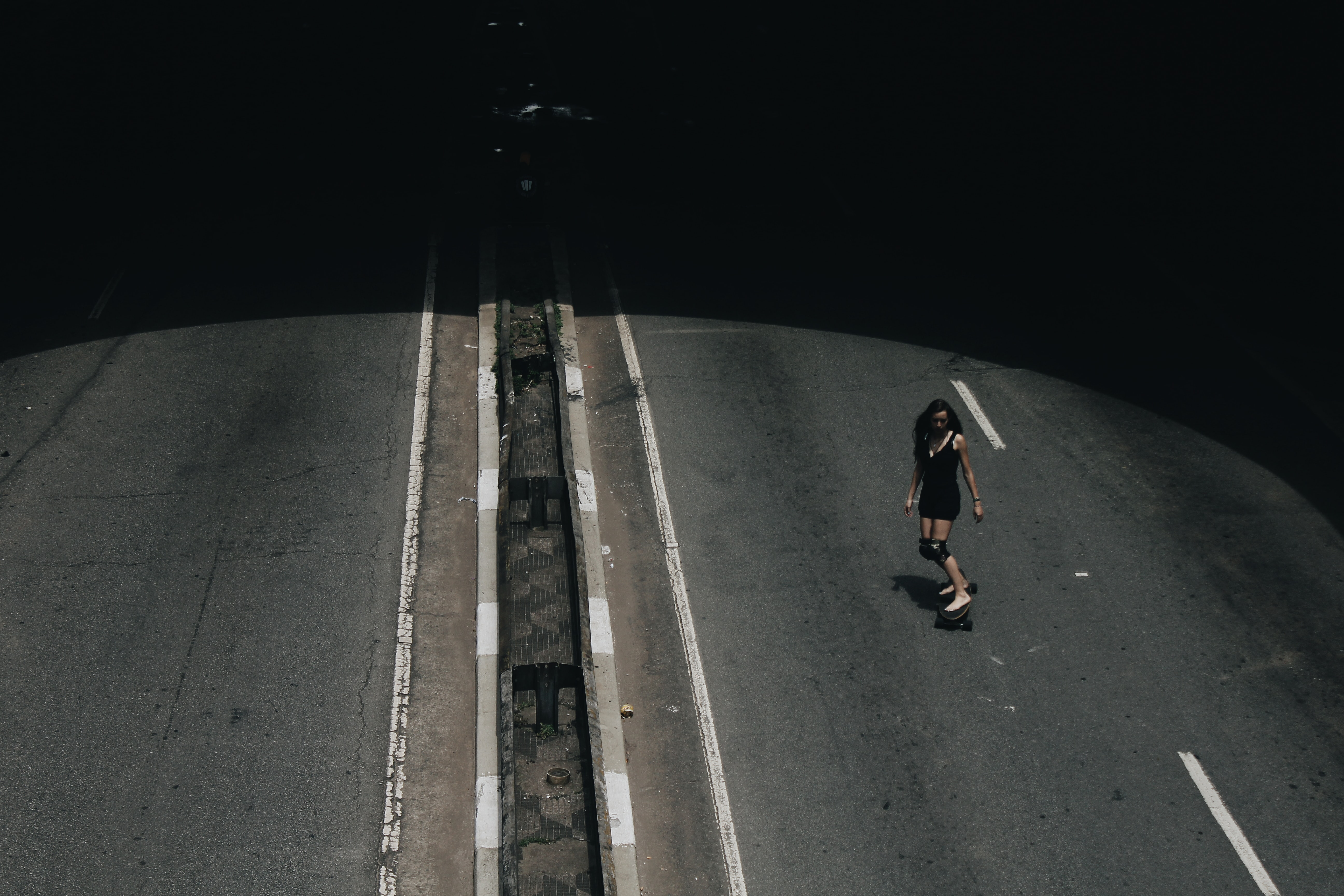 high angle photo of woman riding on skateboard passing road