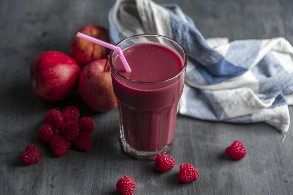 strawberry juice beside strawberry fruits