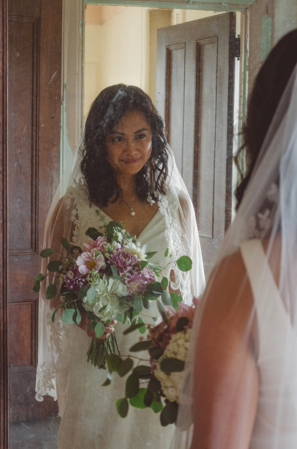 smiling woman in front of mirror wearing white wedding gown and holding flowers