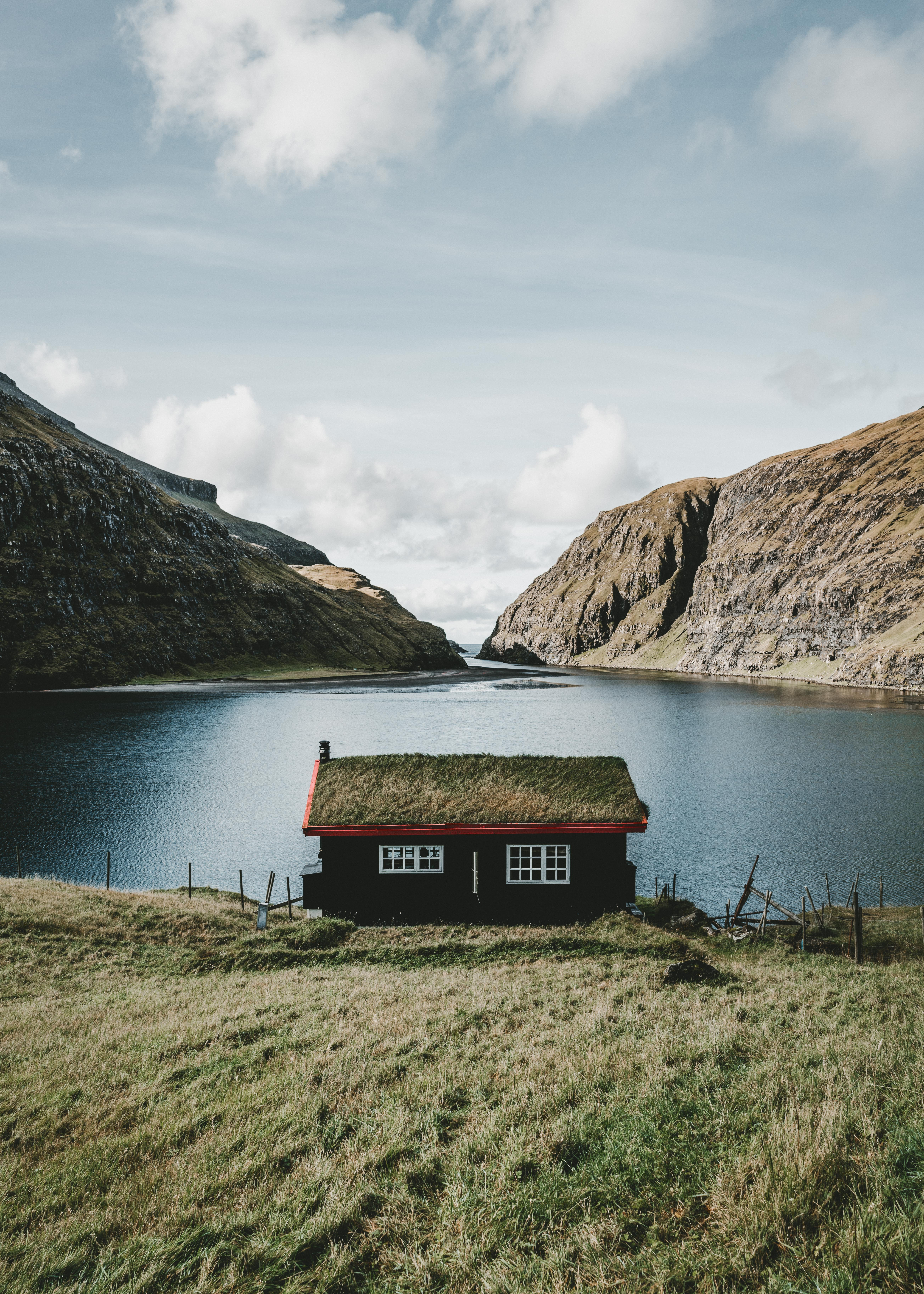 brown wooden shed near body of water across hill at daytime
