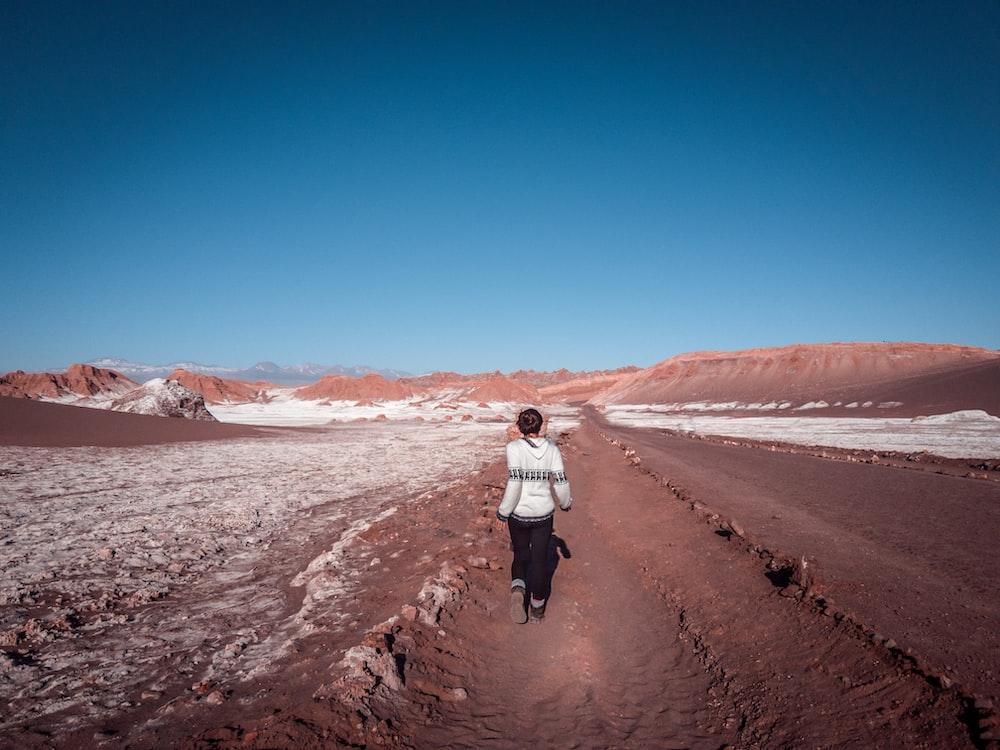 woman walking along dessert under blue sky during daytime