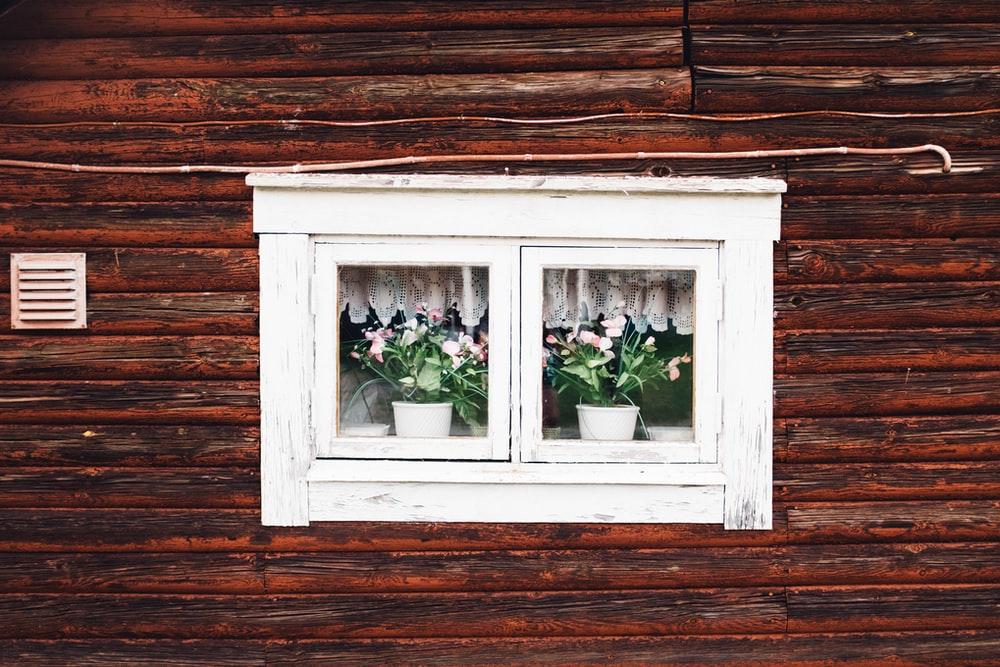 two white plant pots near window