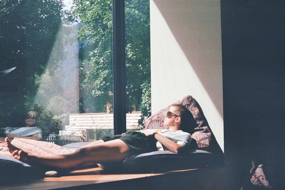 man lying on cushion beside glass window