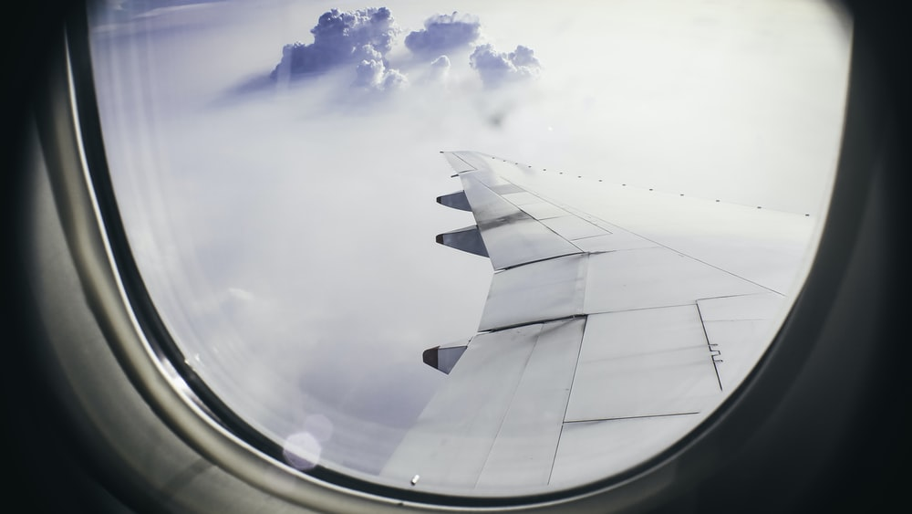 architectural photography of plane's wing above clouds during flight