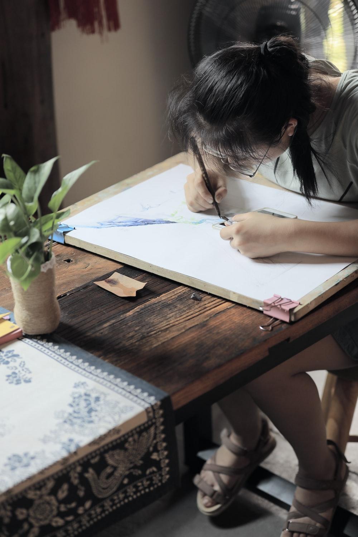 girl doing artwork on board inside well lit room